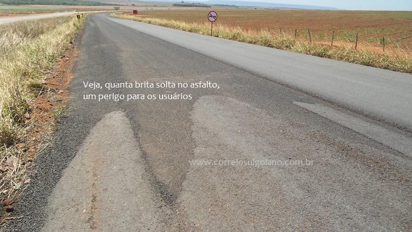 Desnível e brita solta no asfalto sem faixas
